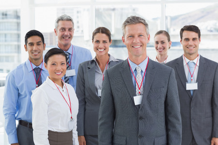 mature business man: Happy business people looking at camera in office