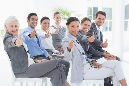 personas mirando: La gente de negocios mirando a la c�mara con los pulgares para arriba en la oficina