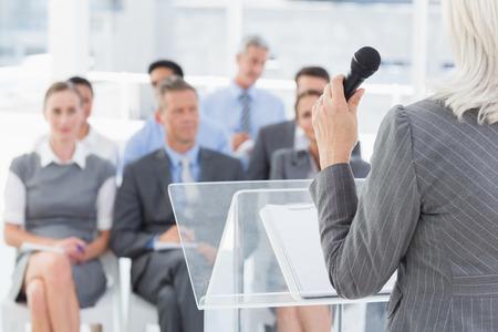 mature business man: Businesswoman doing speech during meeting in office