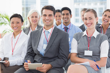 happy business team: Smiling business people looking at camera during meeting in office Stock Photo