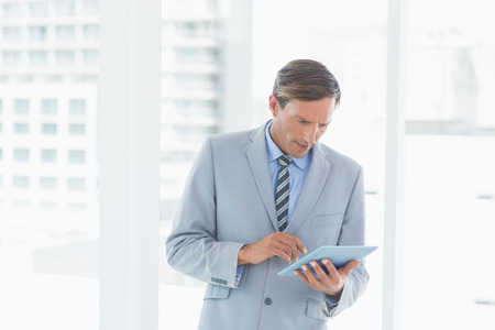concentrate on: Concentrate businessman using tablet pc in office