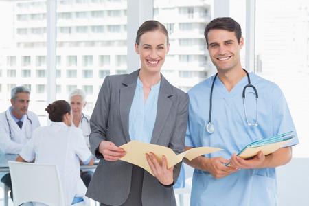 uniformes de oficina: Médicos masculinos y femeninos con los informes en los hospitales