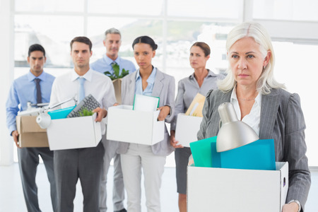 unhappy people: Unhappy fired business people holding box in office
