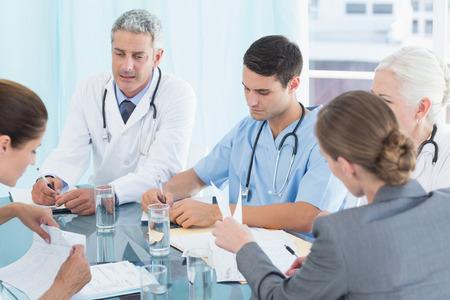 Mannelijke en vrouwelijke artsen werken aan rapporten in de medische kantoor