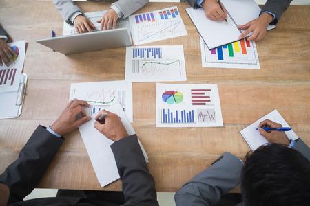 reuniones empresariales: Gente de negocios en reuni�n de sala de juntas que estudian algunos gr�ficos