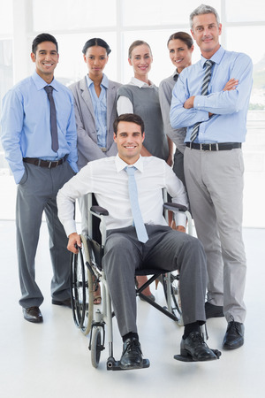 wheelchair: Businessman in wheelchair with his colleagues looking at camera in office