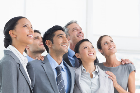 african american woman smiling: Happy young business people looking up in the office