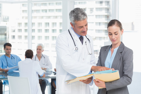 office uniform: Male and female doctors working on reports in medical office Stock Photo