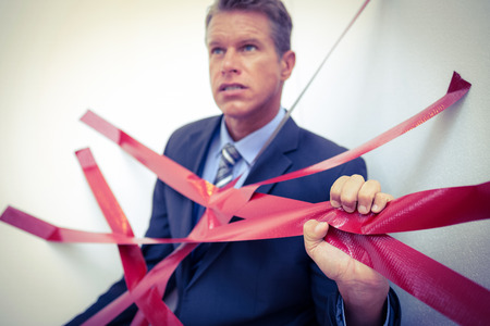 trapped: Businessman trapped by red tape on white background
