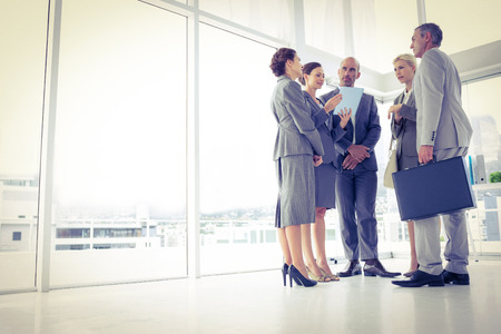 business attire: Business team standing and speaking in the office Stock Photo