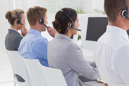 center agent: Business team working on computers and wearing headsets in call center
