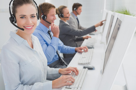 mid adult women: Business team working on computers and wearing headsets in call center