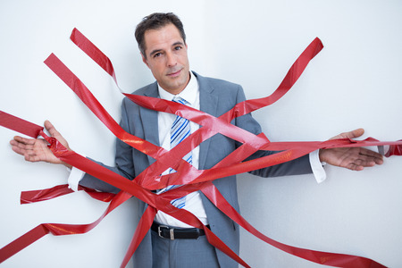 are trapped: Businessman trapped by red tape on white background