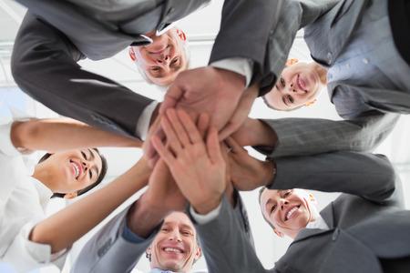 personas trabajando en oficina: Equipo de negocios de pie manos juntas en la oficina