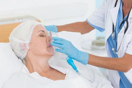 ox�geno: Doctor que pone una m�scara de ox�geno en el hospital Foto de archivo