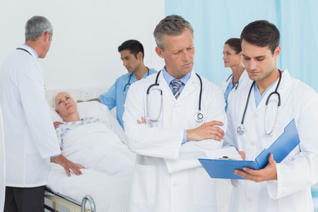hospital patient: Report reading with colleagues and patient behind at hospital