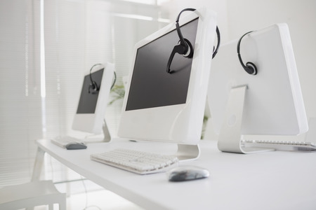 computers office: Computers and headsets in empty office