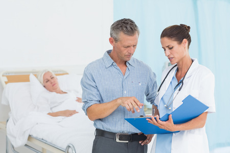 hospital patient: Doctor explaining report to female patient and husband in the hospital