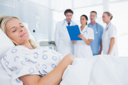 dormir: Dormir paciente con médicos atrás en la habitación del hospital Foto de archivo