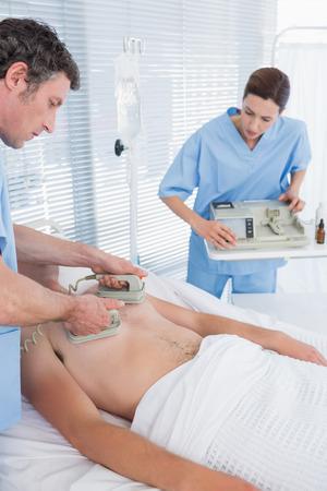 defibrillator: Medical team resuscitating a man with a defibrillator in hospital room Stock Photo