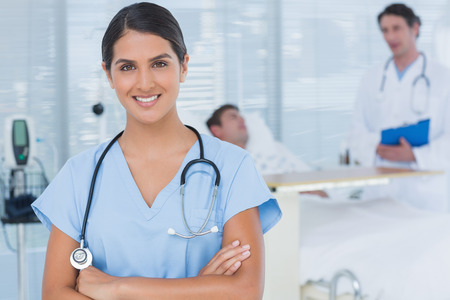 keep watch over: Smiling doctor looking at camera in patients room