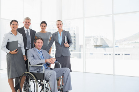 wheelchair: Disabled businessman with his colleagues smiling at camera in the office Stock Photo