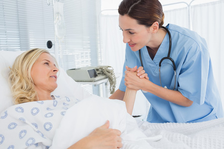 recovery bed: Doctor taking care of patient in hospital room Stock Photo