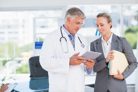 Überzeugter Doktor und hübsche Geschäftsfrau diskutieren in Arztpraxis Standard-Bild