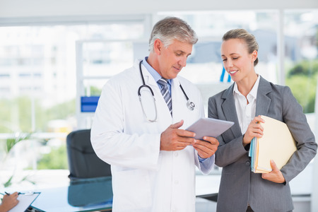 medical office: Confident doctor and pretty businesswoman discussing in medical office