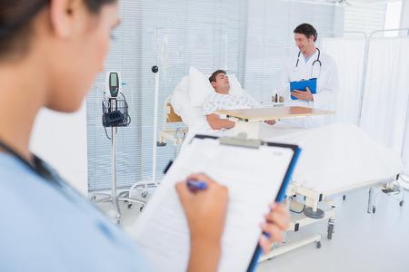 Artsen die voor patiënt in het ziekenhuisruimte zorgen
