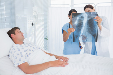 keep watch over: Doctors examining patients xray in hospital room Stock Photo