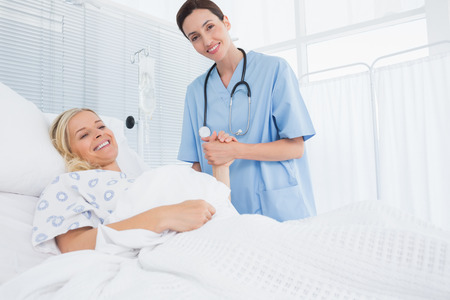the patient: Doctor taking care of patient in hospital room Stock Photo