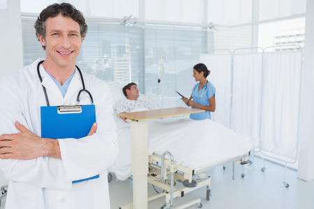 keep watch over: Smiling doctor holding patients file in hospital room