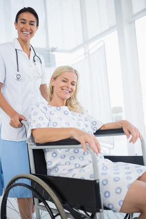 paraplegico: Médico y el paciente en silla de ruedas sonriendo a la cámara en el hospital