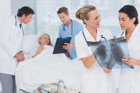 Doctors discussing about patients file in hospital room