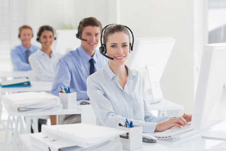 business executive: Business team working on computers and wearing headsets in call center