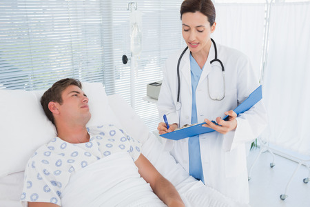 hospital patient: Doctor taking care of patient in hospital room Stock Photo