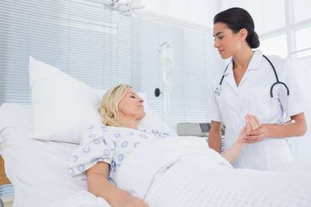 taking care: Doctor taking care of patient in hospital room Stock Photo