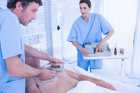 rhythms: Medical team resuscitating a man with a defibrillator in hospital room Stock Photo