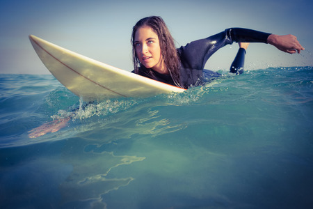 wetsuit: woman in wetsuit surfing on sunny day