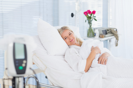 recuperation: Happy patient lying on her bed in hospital Stock Photo