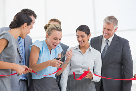 ribbon cutting: Happy business team cutting red ribbon in the office