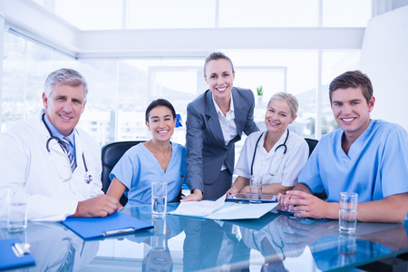 male doctor: Team of doctors and businesswoman having a meeting in medical office