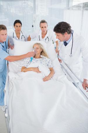 paciente en camilla: Equipo de m�dicos que llevan al paciente sobre la camilla en el hospital