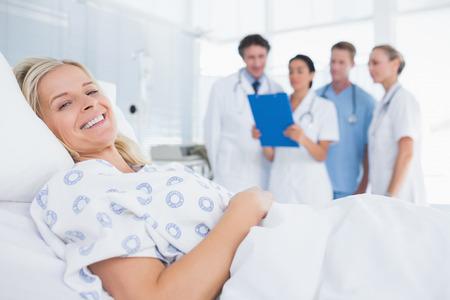 mujer en la cama: Paciente sonriente mirando a la cámara con los médicos atrás en la habitación del hospital
