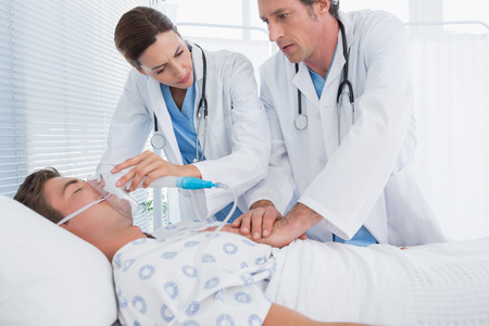 keep watch over: Worried doctors doing heart massage and holding oxygen mask in hospital room