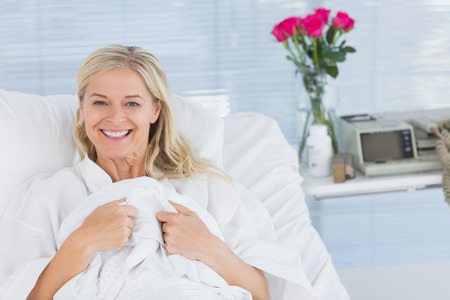 happy patient: Smiling patient looking at camera on her bed in hospital Stock Photo