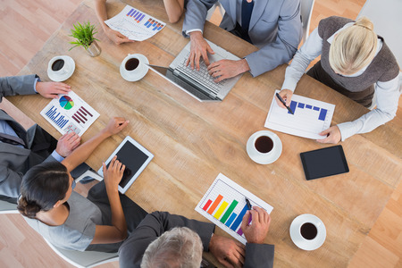 attire: Business team discussing the graphs in the office Stock Photo