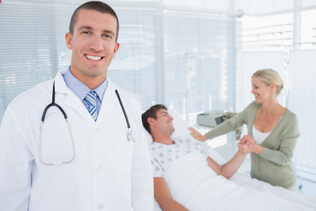 mature doctor: Smiling doctor looking at camera with his patient behind in hospital room Stock Photo