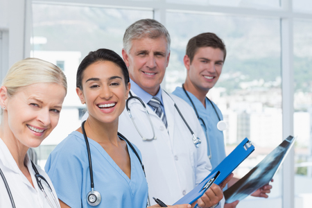medical doctors: Team of smiling doctors looking at camera in medical office